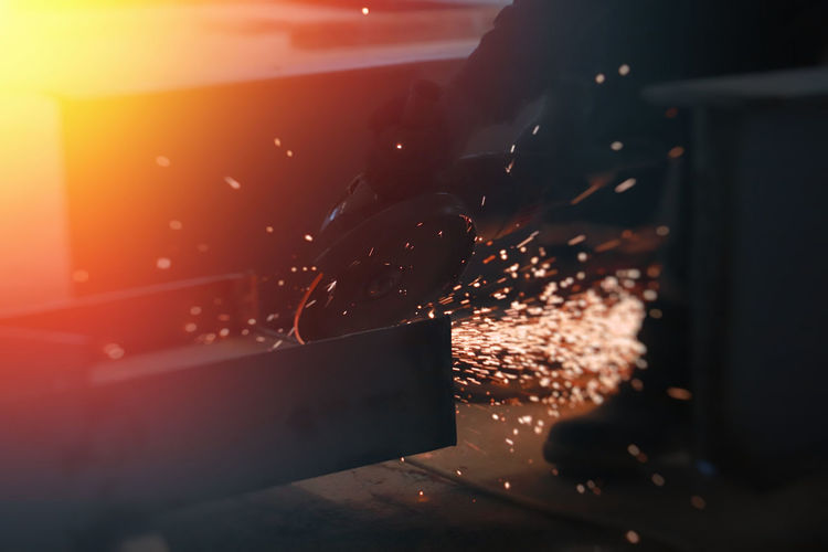 Low section of person grinding metal at workshop