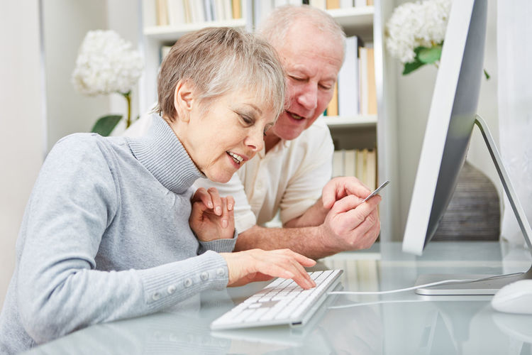 Rear view of man and woman using mobile phone while sitting on table