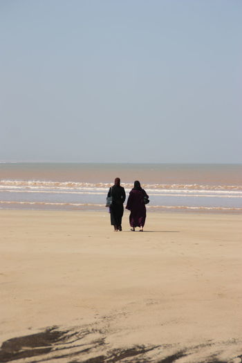 Rear view of female friends walking at beach against clear sky