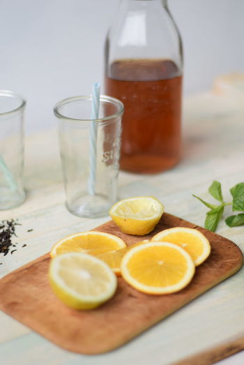 Slice lemons on wooden board by drinking glass with straws and jar of honey