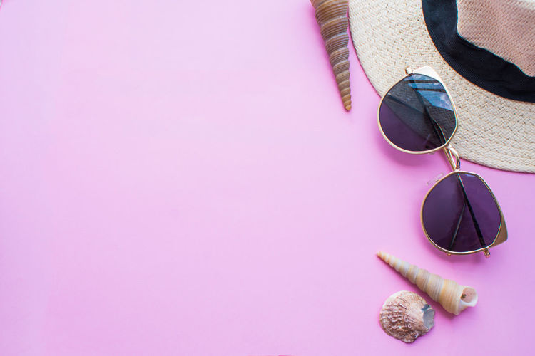High angle view of sunglasses with hat and seashell on table