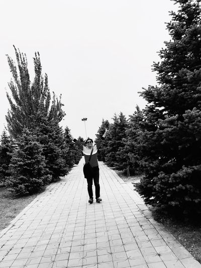 Rear view of woman walking on footpath amidst trees against sky