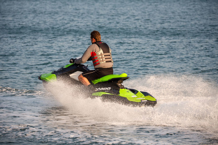 Middle aged man wearing a life vest rides a personal water craft Jet Ski along a calm sea. Jet Ski Water Sport Adventure Aquatic Sport Day Leisure Activity Life Jacket Life Vest Lifestyles Male Men Motion Nature One Person Outdoors Personal Water Craft Real People Sea Sport Water