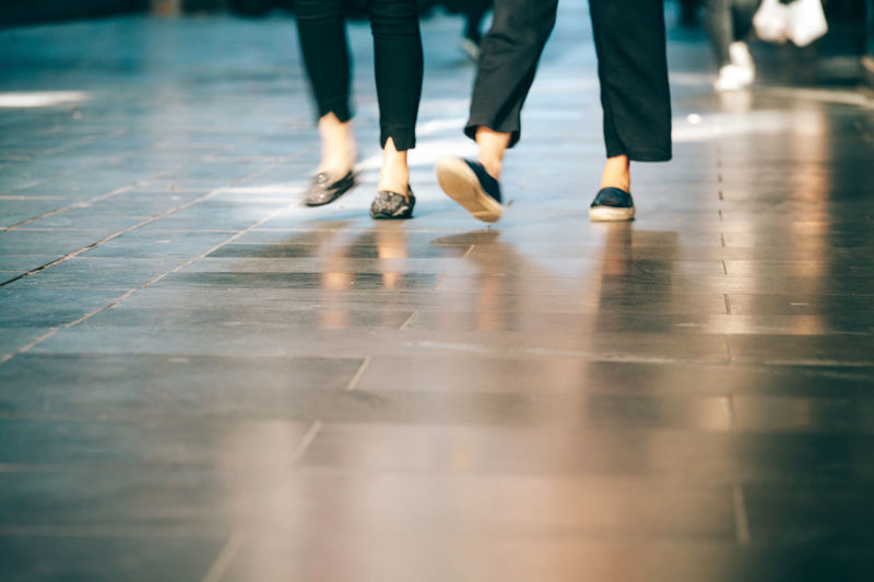 Low section of women walking on floor