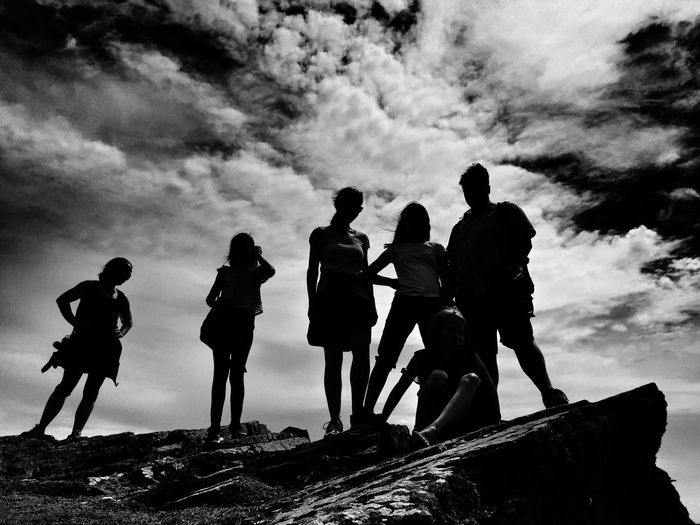 Silhouette Of People Standing On Mountain Against Cloudy Sky