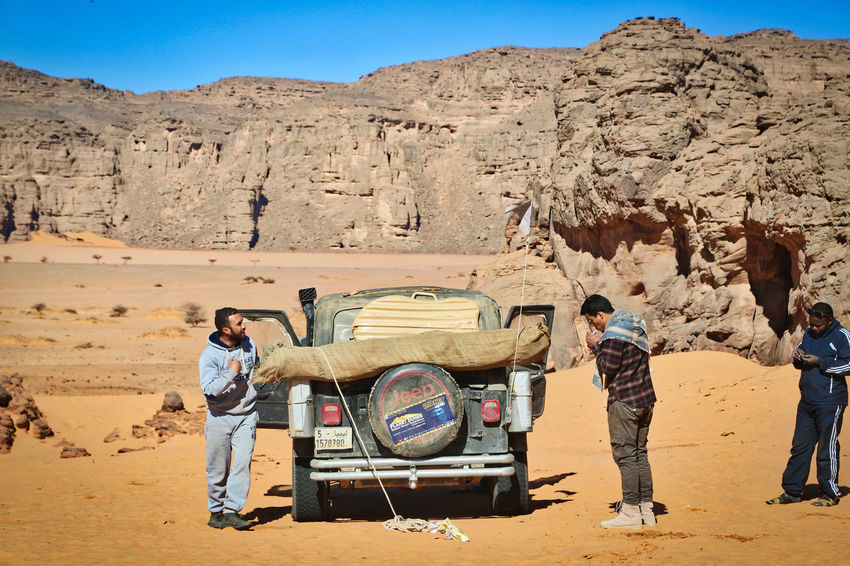 Tadrart Djanet Tour Jeep Adventure 4x4 Adventure Arid Climate Clear Sky Day Desert Full Length Landscape Men Nature Outdoors People Real People Sand Sky Standing Sunlight Togetherness Transportation Young Adult
