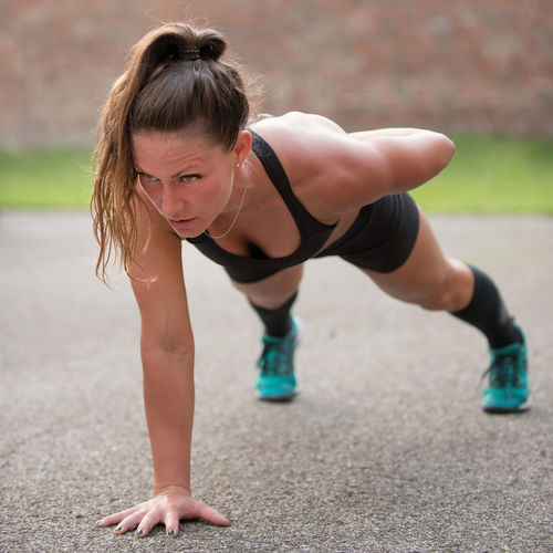 Mid Adult Woman Doing Push-Ups On Road
