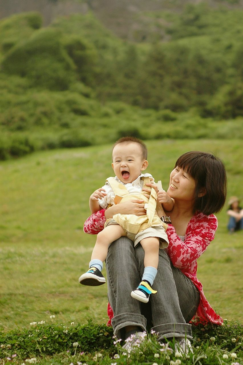 Smiling Mother With Son Sitting On Field