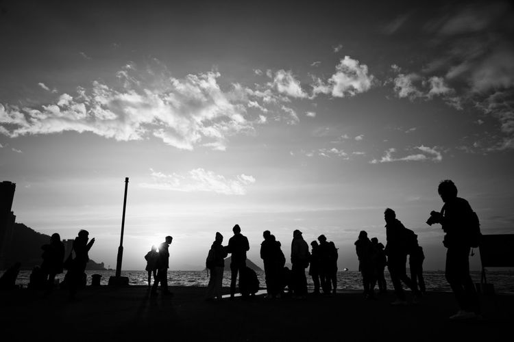 Silhouette people standing against sky during sunset