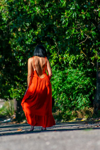 Rear view of female model standing on road against trees