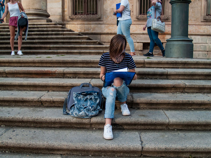 Teenage girl looking at file while sitting on staircase