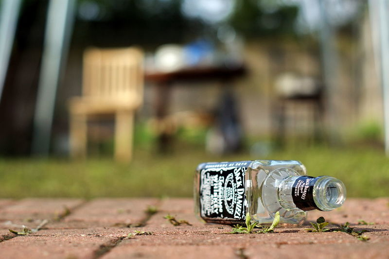 Focus On Foreground Day Architecture Container Built Structure Building Exterior Outdoors Close-up Wood - Material No People Plant Selective Focus Bottle Nature Grass Land Building Residential District Metal Retaining Wall Jack Daniel's Whiskey Sashalmi