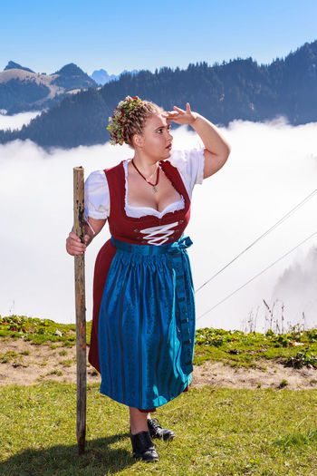 Young woman standing on field against mountains