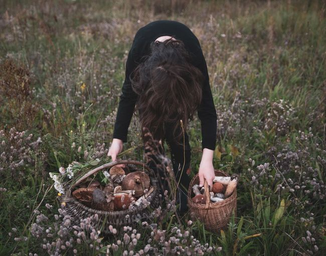 Woman bending with mushrooms in baskets on grassy field