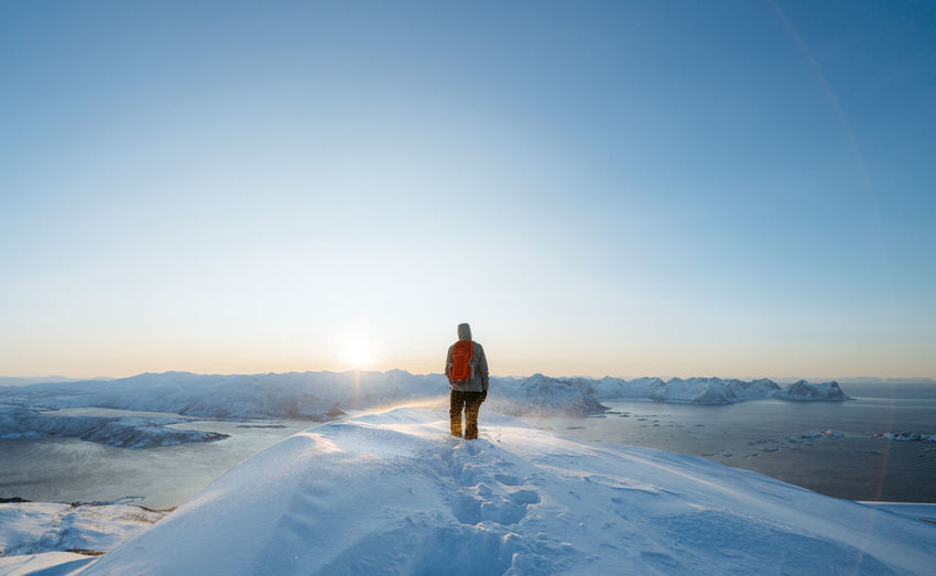 Rear View Of Mid Adult Man With Backpack Standing On Snowcapped Mountain Against Clear Sky