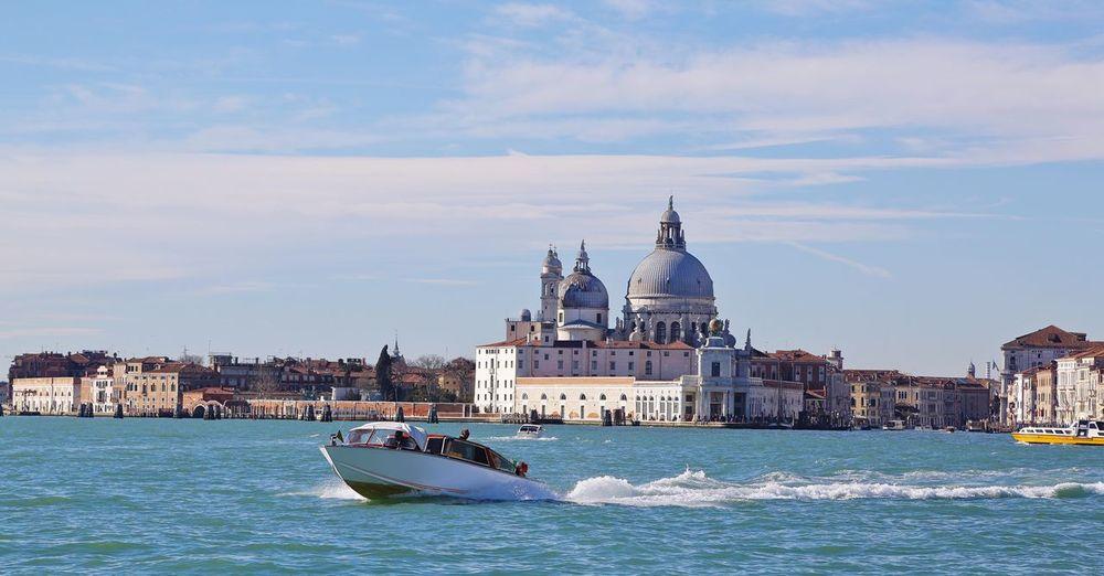 Motorboat in sea with santa maria della salute against sky