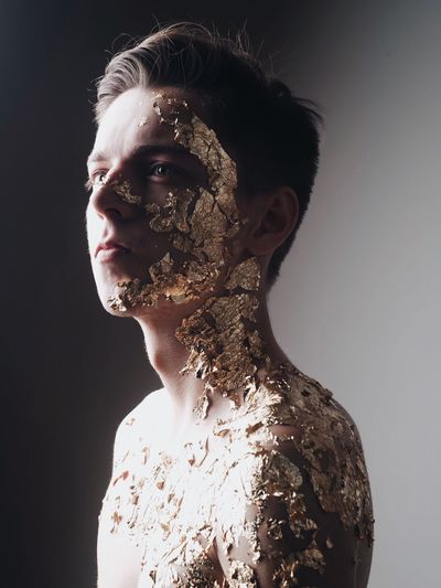 Young Man With Foil On Skin Against Wall