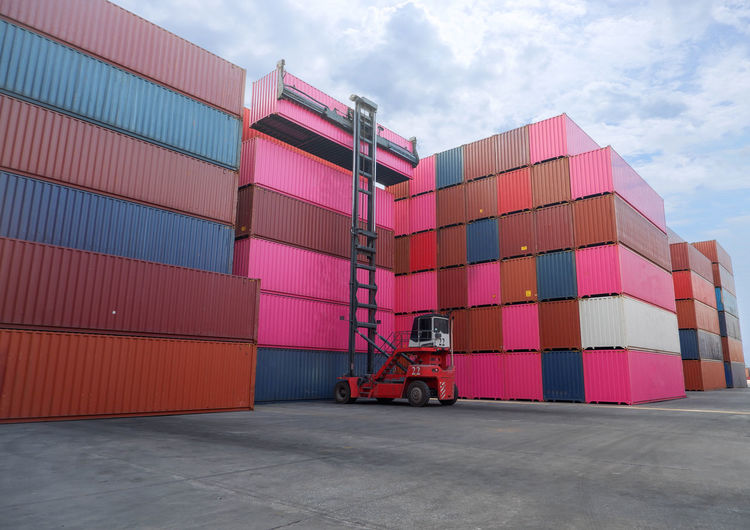 Forklift by containrs stack against sky