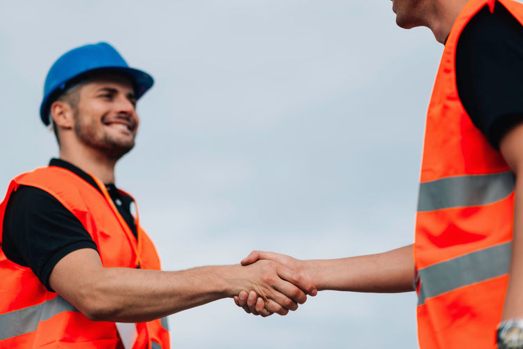 Construction Workers Handshaking On Construction Site Hard Hat Architect Life Business Construction Site Males  Planning Standing Working Caucasian Ethnicity Construction Industry Construction Worker Cooperation Team Work Engineer Handshake Handshaking Manager Orange Color Outdoors Professional Occupation Protective Workwear Site Meeting Sky Smiling Two People Young Men