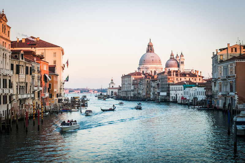 View of Santa Maria della Salute and the Grand Canal at dusk in Venice, Italy Architecture Boat Building Exterior Built Structure Canal Church City Clear Sky Dusk Famous Place Grand Canal Italy Nautical Vessel Place Of Worship Religion River Santa Maria Della Salute Spirituality Tourism Transportation Travel Travel Destinations Water Waterfront
