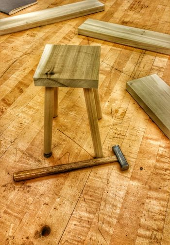 High Angle View Of Hammer By Stool At Carpenter Workshop
