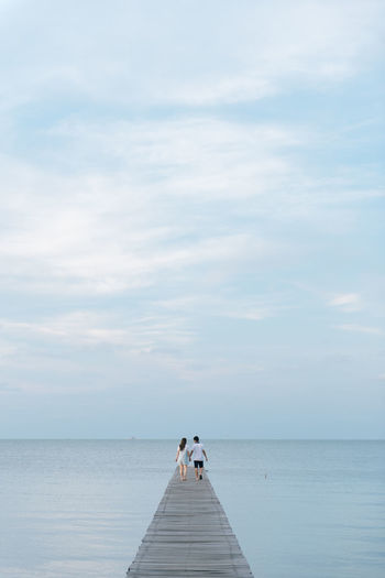 Mid adult couple walking on jetty over sea