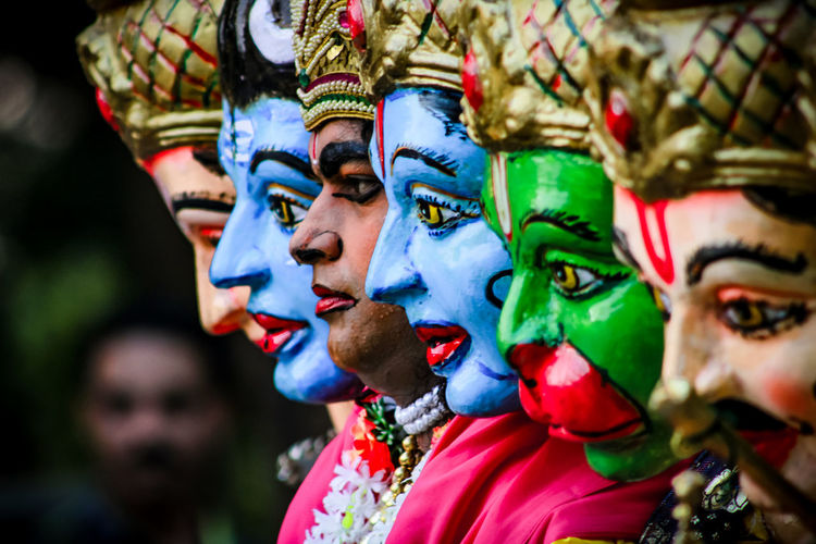 Close-Up Of Man Wearing Various Colorful Masks Looking Away Outdoors