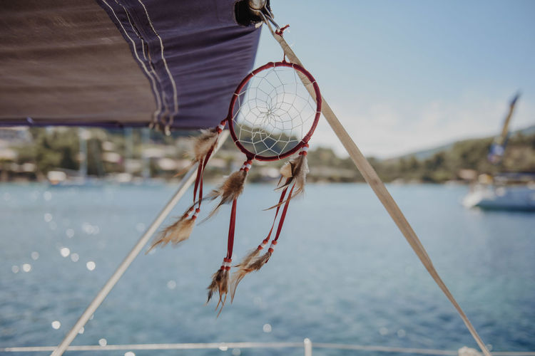Close-up of dreamcatcher hanging on boat in sea