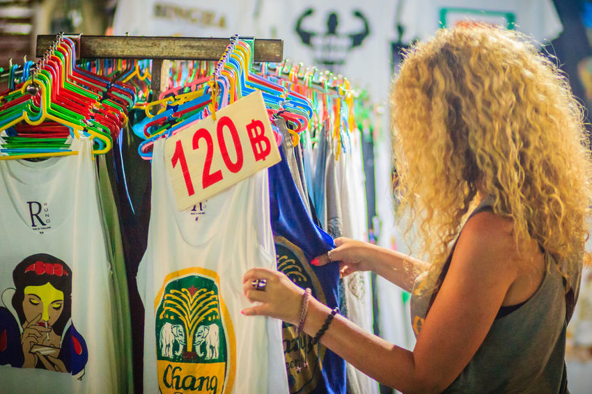 Bangkok, Thailand - March 2, 2017: Tourist selecting for cloths at Khao San Road night market. Woman traveler is shopping at local store shop and looking for colorful clothes during her vacation trip Khao San Rd Khao San Road KhaoSan Khaosan Rd. Shopping Adult Casual Clothing Clothing Clothing Store Day Hair Hairstyle Khao San Khao San Knok Wua Khaosan Road Khaosanroad Leisure Activity Lifestyles Multi Colored Night Market Night Market In Thailand One Person Real People Rear View Retail  Retail Display Sale Selected For Premium Shopping Shopping Time Standing Store Text Waist Up Women