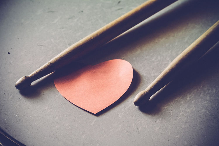 High Angle View Of Sticks With Heart Shape Paper On Drum