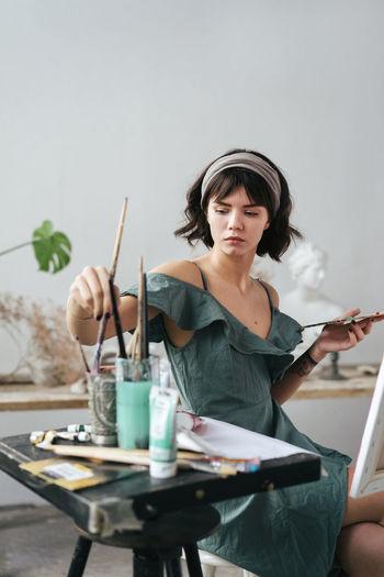 Painter sitting on stool at art studio