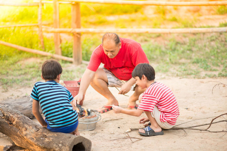 Man And Two Boys Lighting Fire Outdoors