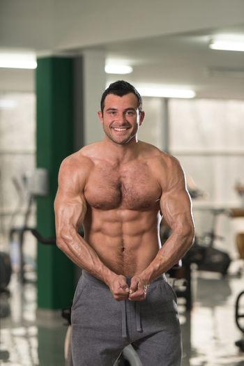Portrait of shirtless man exercising in gym