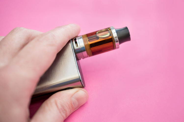 Vape pen electronic cigarette device for vaping Vape Vaping Electronic Cigarette  Pen Device Background View Tank Liquid Juice Metal Silver  Tobacco Smoking Vapor Close-up Pink Hand Adult Using Holding