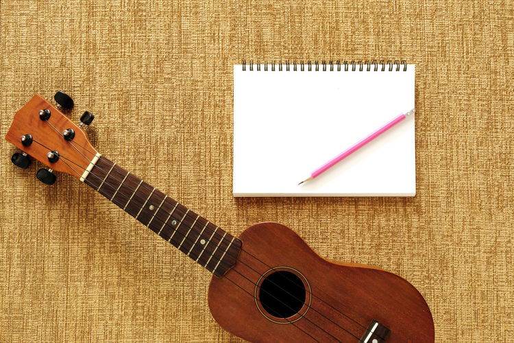Acoustic Guitar Arts Culture And Entertainment Brown Close-up Creativity Directly Above Guitar Indoors  Music Musical Equipment Musical Instrument Musical Instrument String No People Paper Pattern Sheet Stage Still Life String String Instrument Wood - Material