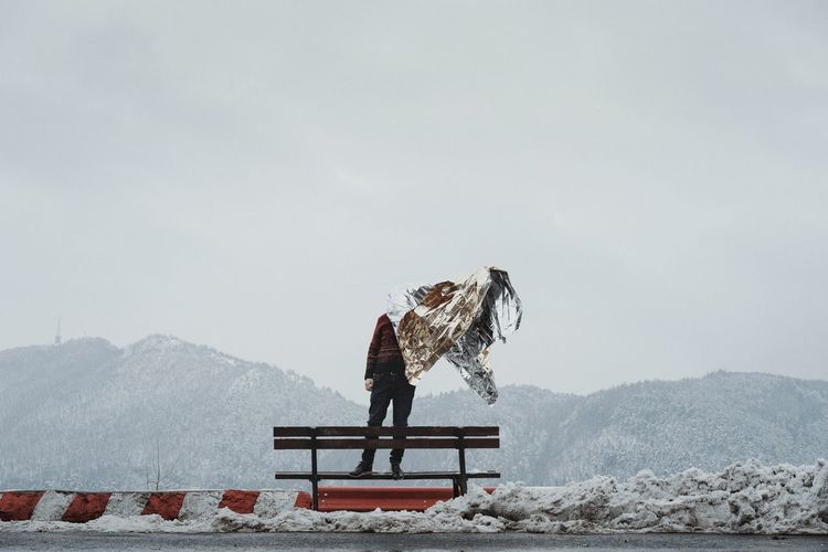 Man Holding Foil While Standing On Bench Against Mountain And Sky During Winter
