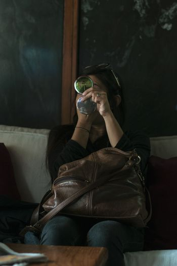 Woman holding sunglasses while sitting on sofa at home
