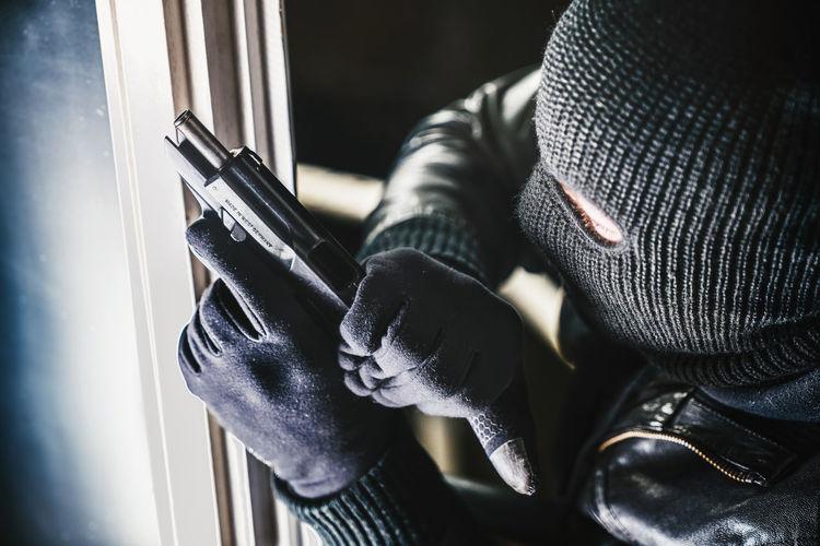 High angle view of burglar with gun standing by window