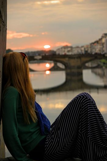 Woman Sitting By Ponte Vecchio Over Arno River Against Sky During Sunset