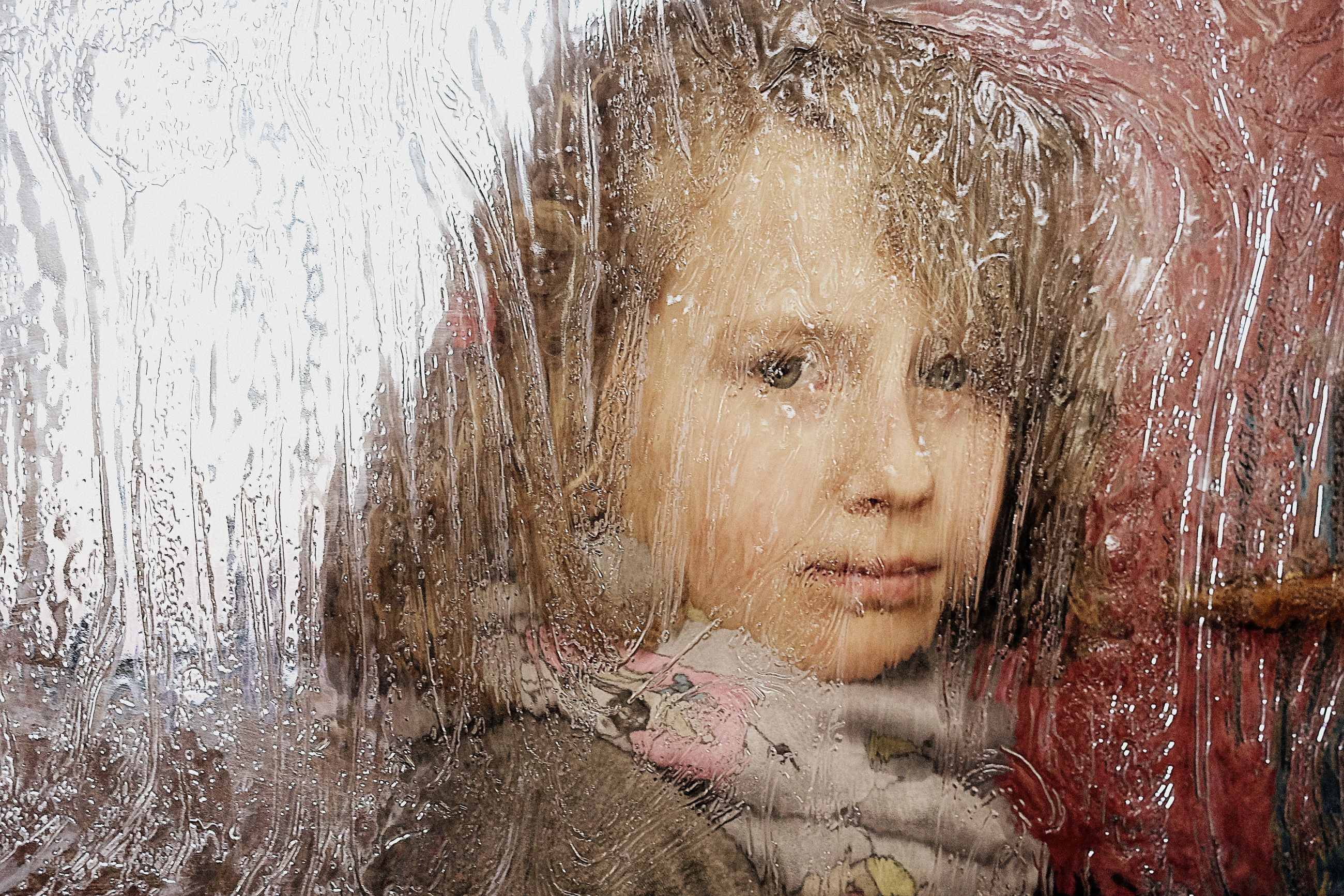 CLOSE-UP PORTRAIT OF WOMAN LOOKING THROUGH WINDOW IN WINTER