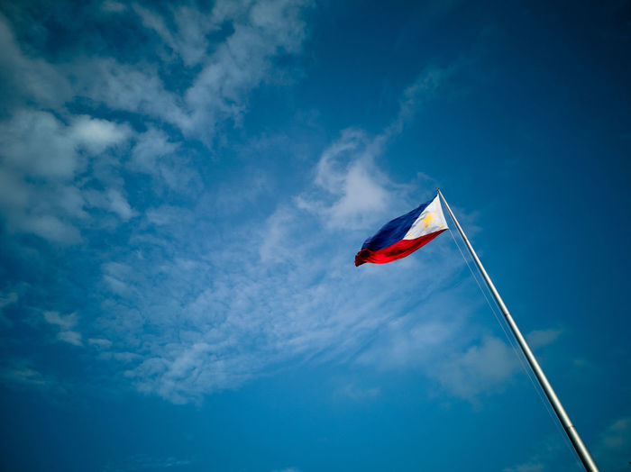 Low angle view of philippines flag against blue sky