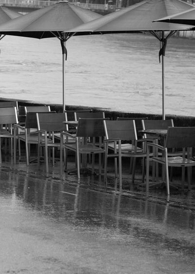 Empty chairs and table at beach during rainy season
