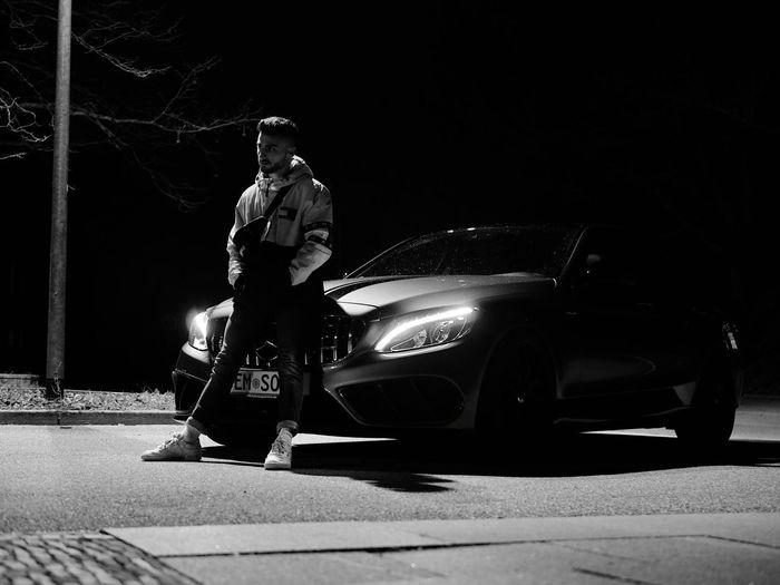 Man standing on street at night