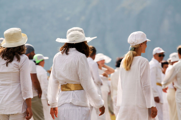 People Wearing White Clothes Standing Outdoors