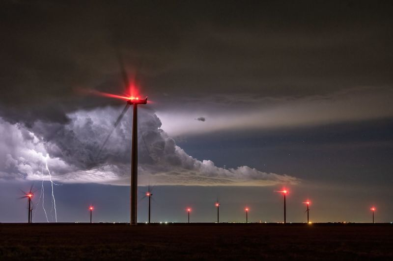 Wind turbines on field against sky at night