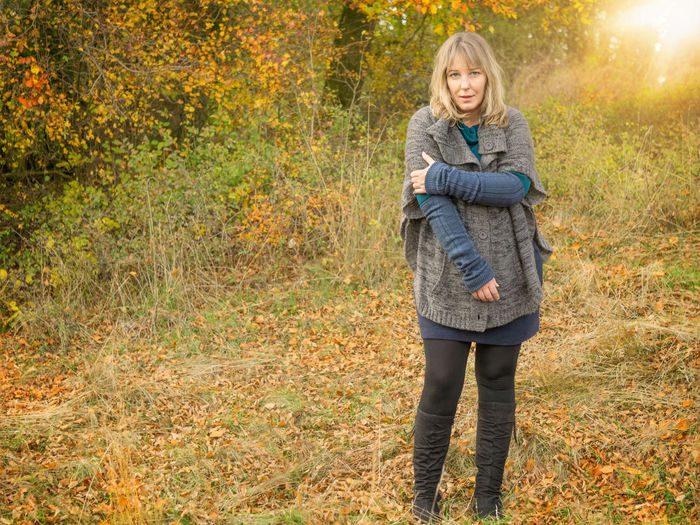Woman looks pertly in autumn scenery Autumn Cardigan Woman Atmospheric Autumn Autumn Scenery Blond Hair Blond Hair Challenging Cord Forest Full Length High Boots Leaf Looks Into The Camera Middle Aged Nature One Person Pert Look Poncho Skirt Sock Trousers Spanning Standing Tense Shoulder