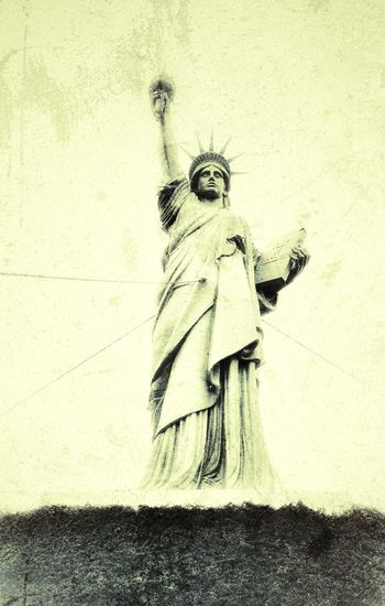 Statue of woman standing against wall