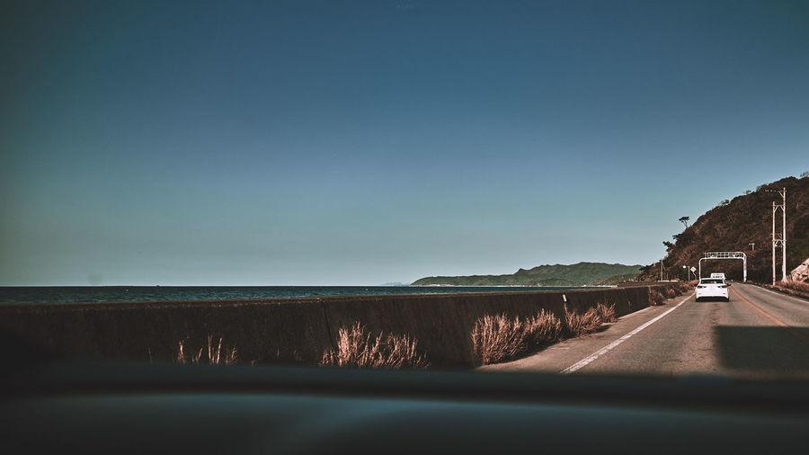 Road by sea seen through car windshield