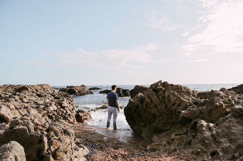 Rear view of young man standing at rocky shore against sky