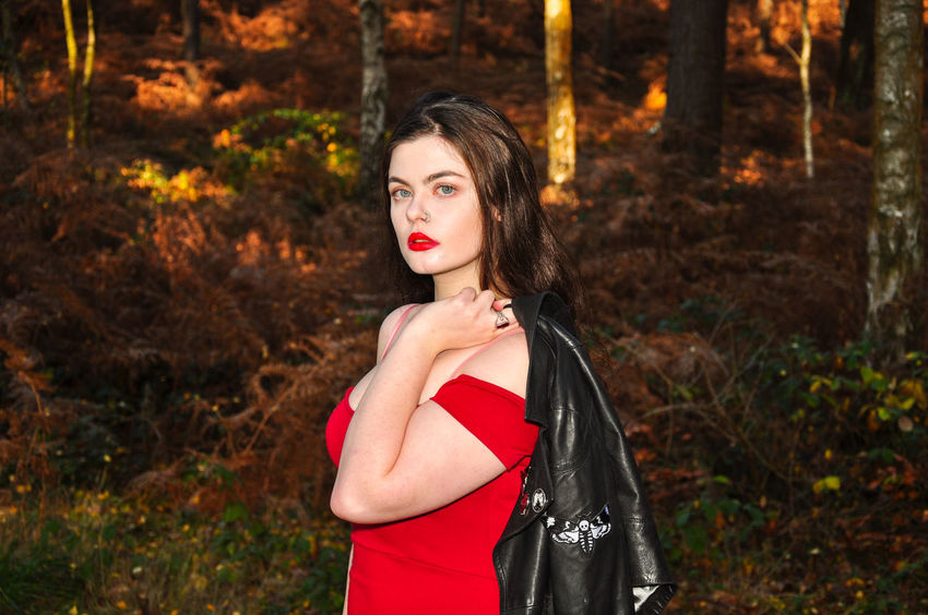 Beautiful young lady in a red dress in the forest Girl Millenial Young Lady Red Dress Red Red Color Red Lipstick Forest Trees Beauty Beautiful Woman Beautiful Long Hair Black Leather Jacket Stunner Beautiful Young Lady Beautiful Young Woman Autumn Autumn colors autumn mood One Person Portrait Young Adult Women Dress Hair Young Women Waist Up Glamour